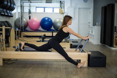 Determined woman practicing stretching exercise on reformer stock image
