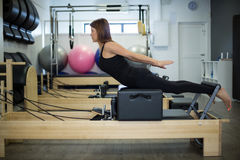 Determined woman practicing stretching exercise on reformer royalty free stock photo