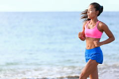 Determined Woman Running On Beach. Determined woman jogging on beach. Fit young female is in sports clothing. Jogger is exercising against ocean during sunny day Stock Images