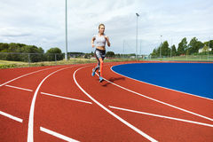 Determined Woman Running On Sports Tracks. Full length of determined woman running on sports tracks Stock Image