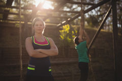 Determined woman standing with arms crossed during obstacle course stock photography
