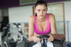 Determined woman working out at spinning class Stock Photography