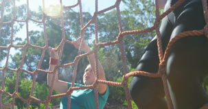 Determined women climbing a net during obstacle course stock footage
