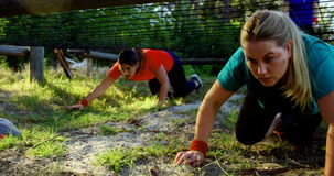 Determined women crawling under the net during obstacle course