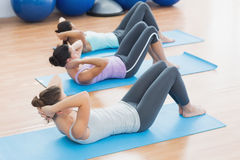 Determined women doing sit ups at fitness studio Stock Image
