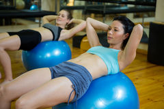 Determined women exercising on fitness ball Stock Photos