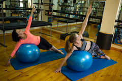 Determined women exercising on fitness ball Royalty Free Stock Images