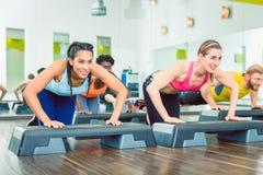 Determined women exercising push-ups on aerobic stepper platform stock photo