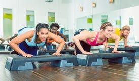 Determined women exercising push-ups on aerobic stepper platform stock image