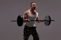 Determined young athlete exercising with a barbell Stock Photo