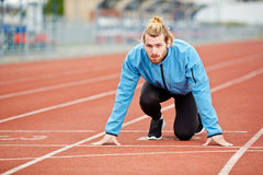 Determined young athlete on starting line at track and field stadium Stock Images