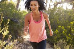 Determined young black woman jogging in a forest, close up Royalty Free Stock Image