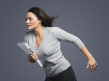 Determined Young Businesswoman Running Into Wind. Determined young businesswoman running into the wind against gray background Royalty Free Stock Image