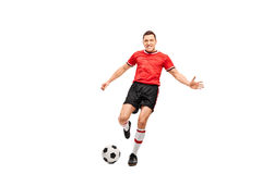 Determined young football player shooting a ball Royalty Free Stock Photo