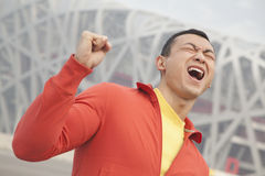 Determined young man in athletic clothing with fist in the air, with modern building in the background in Beijing, China Royalty Free Stock Image