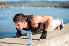 Determined young man doing push-ups on a riverbank royalty free stock photography