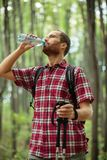 Determined young man hiking through forest, drinking water and resting royalty free stock photo