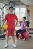 Determined young man holding ball in the gym, people working out in the background Royalty Free Stock Images