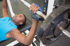 Determined young man lifting barbell in gym Royalty Free Stock Images