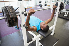 Determined young man lifting barbell in gym Royalty Free Stock Photo