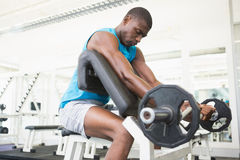 Determined young man lifting barbell in gym Stock Photo