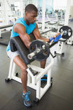 Determined young man lifting barbell in gym Stock Image