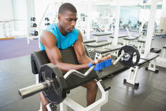 Determined young man lifting barbell in gym Stock Photography