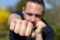 Determined young man punching at the camera Stock Photo
