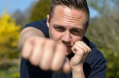 Determined young man punching at the camera Stock Photography