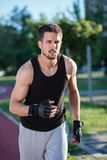 Determined young man running in the park royalty free stock image