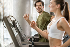 Determined young man smiling while running on treadmill during h Stock Photos