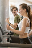 Determined young man smiling while running on treadmill during h Royalty Free Stock Photo