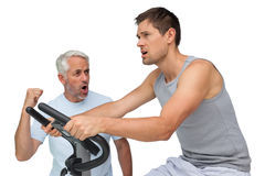 Determined young man on stationary bike with trainer Stock Photography