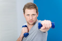 Determined young man working out with weights stock photos