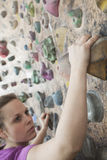 Determined young woman climbing up a climbing wall in an indoor climbing gym Royalty Free Stock Photo