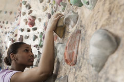 Determined young woman climbing up a climbing wall in an indoor climbing gym Stock Photo