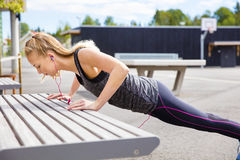 Determined Young Woman Doing Pushups On Bench stock image