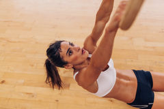 Determined young woman exercising with gymnastic rings Stock Photo