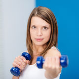 Determined young woman lifting weights Stock Image