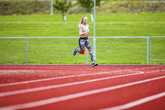 Determined Young Woman Running On Sports Tracks royalty free stock photography