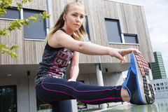 Determined Young Woman Stretching Her Leg Against Building Royalty Free Stock Photo