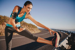 Determined young woman warming up before a run. Female athlete stretching her leg on road guardrail in morning Royalty Free Stock Image