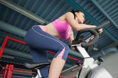 Determined young woman working out at spinning class Stock Photo