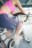 Determined young woman working out at spinning class Stock Photography