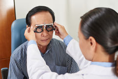 Determining diopter. Female ophthalmologist precisely determines diopter for senior man Stock Photography