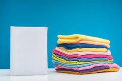 Detersivo di lavanderia e vestiti puliti che si trovano sulla tavola immagine stock