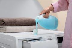 Detersivo di lavanderia di versamento della donna nel cappuccio sulla lavatrice all'interno fotografia stock