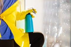 Detersivo di spruzzatura di pulizia di finestra della persona fotografia stock