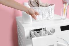 Detersivo di versamento della donna nel cassetto della lavatrice nella stanza di lavanderia fotografia stock libera da diritti