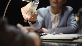 Detetive fêmea que mostra o dinheiro do dinheiro ao suspeito, interrogação do traficante de drogas video estoque
